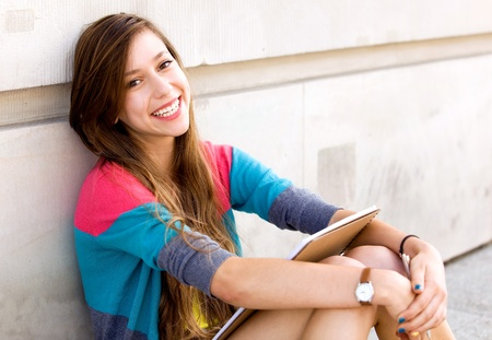 young teen girl: Girl sitting by the wall