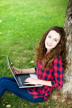 Woman using a laptop under a tree Stock Photo - 10567602
