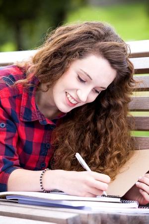 Girl doing her homework outdoors photo