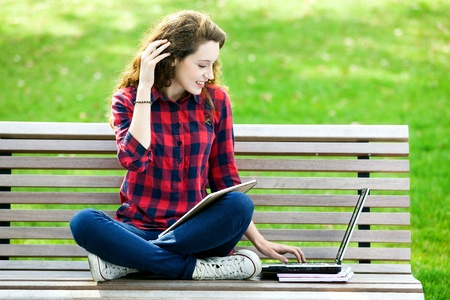 Girl using a laptop on a bench Stock Photo