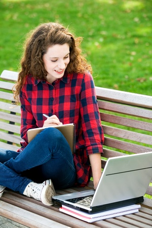 Girl using a laptop on a bench photo