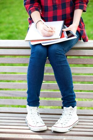 adult  body writing: Female student sitting on a bench