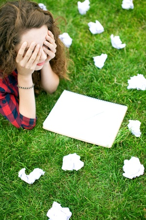 upset woman: Female Student Surrounded by Crumpled Paper Stock Photo