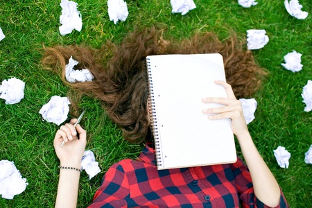 frustrated student: Female Student Surrounded by Crumpled Paper Stock Photo