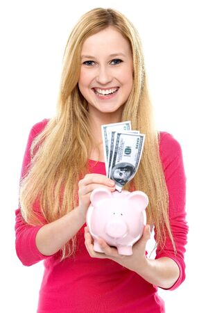 putting in: Woman putting money in piggy bank Stock Photo