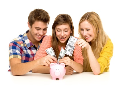 Young people putting money in piggy bank photo