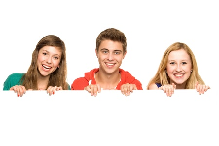 teenagers laughing: Friends holding blank poster