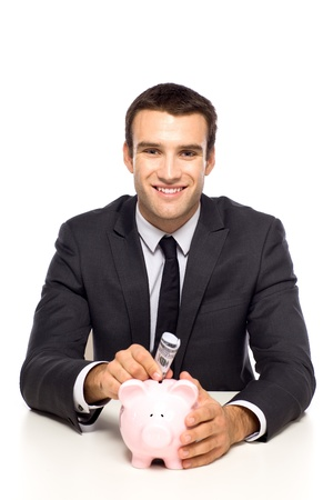 Businessman putting money in piggy bank photo
