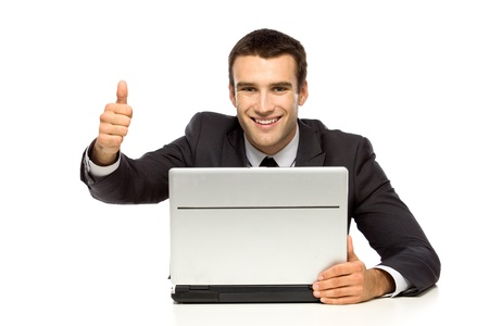 Businessman with laptop showing thumbs up photo