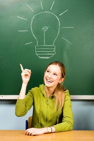 student desk: Female student and light bulb on chalkboard