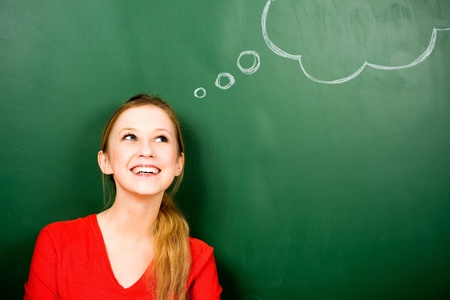 daydreaming: Woman standing next to thought bubble on blackboard Stock Photo