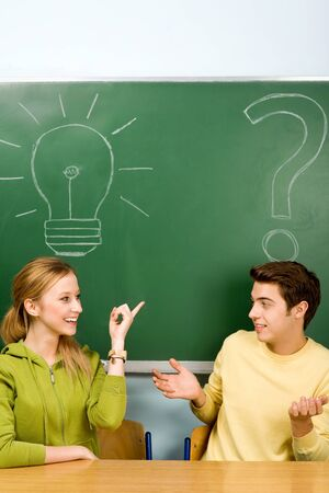 Two students with light bulb and question mark on chalkboard photo