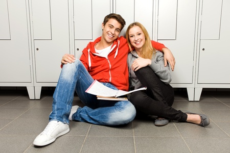 Students sitting by lockers in school corridor photo
