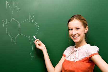 chemistry lesson: Student writing chemical symbol on blackboard