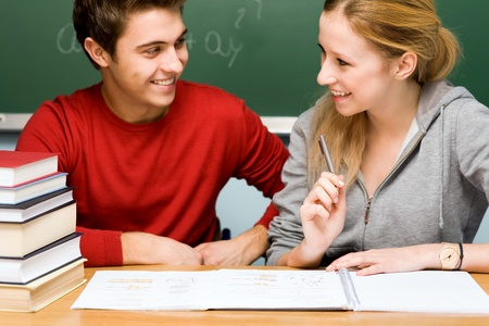 Couple working together on school work in classroom photo