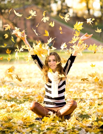 Woman throwing autumn leaves  photo