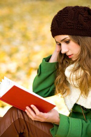 Girl reading book outdoors photo