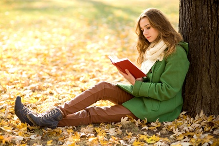 Girl reading book outdoors photo