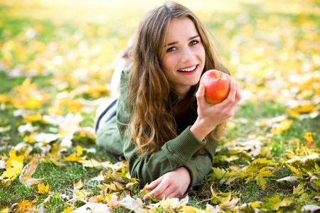 lying down: Woman eating apple outdoors in autumn