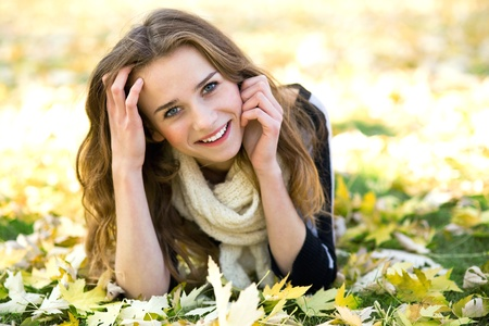 Girl surrounded by autumn leaves Stock Photo - 11322565