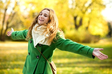 Woman with arms outstretched outdoors Stock Photo