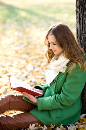 Young woman reading book in the park photo