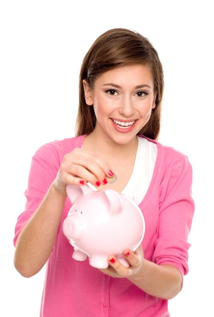 Girl putting coin in piggy bank photo
