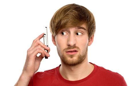 persona confundida: Confundido hombre con el tel�fono m�vil Foto de archivo