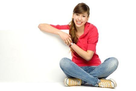 Young woman leaning on blank poster photo