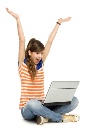 woman sitting with laptop: Woman with arms raised using laptop