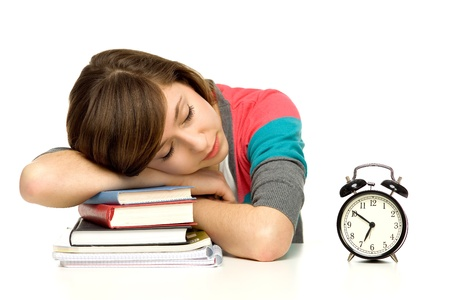 sleeping at desk: Female student sleeping next to alarm clock Stock Photo