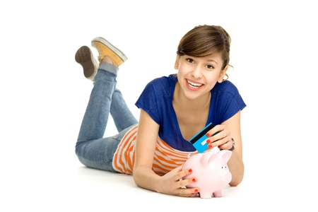 Woman putting credit card into piggy bank photo