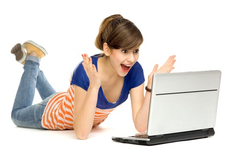 amazement: Surprised young woman using laptop
