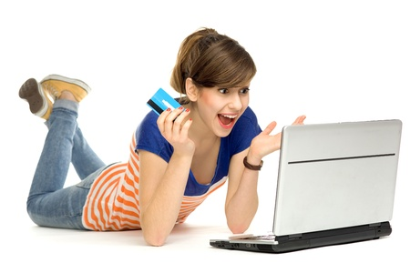 amazement: Surprised woman with credit card and laptop Stock Photo