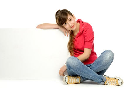 Teenage girl leaning on blank poster photo