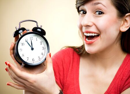 ticking: Young woman holding alarm clock