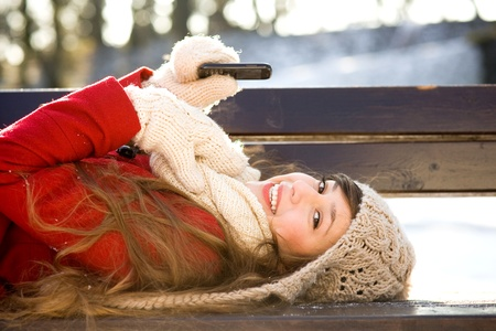 Woman lying on bench with mobile phone photo