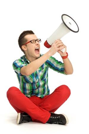 Young man shouting through megaphone Фото со стока