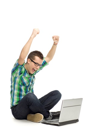 Guy using laptop with arms raised photo