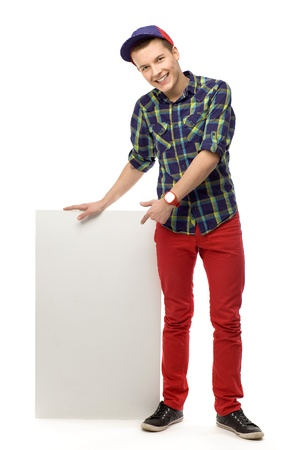 Adolescente que señala en cartel en blanco Foto de archivo