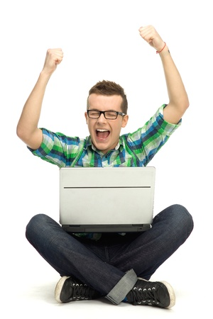 Guy using laptop with arms raised Stock Photo - 12378423