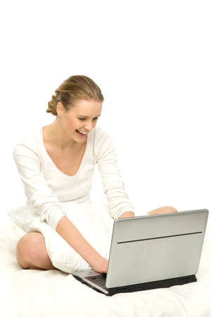 Woman using laptop in bed photo