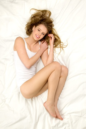 undergarments: Young woman lying on bed