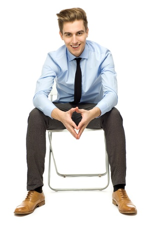 sitting on: Handsome young man sitting  Stock Photo