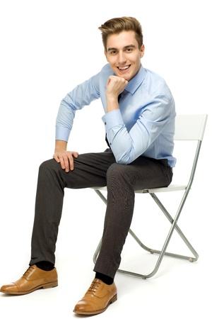 personas sentadas: Apuesto joven sentado Foto de archivo