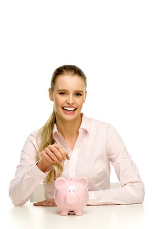 Woman putting money in piggy bank photo
