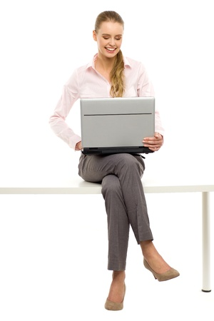 Woman sitting on table with laptop Stock Photo - 12964376