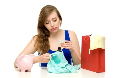 Unhappy woman with shopping bags and piggybank photo
