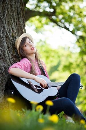 Frau spielt Gitarre im Park Standard-Bild