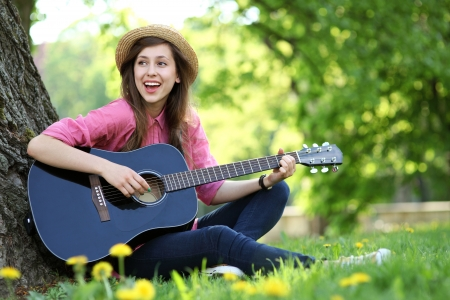 girl playing guitar: Woman playing guitar in park